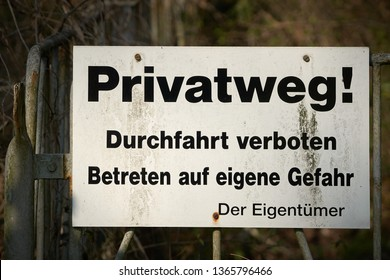 "Sign on a fence with the words ""Private road, passage forbidden, entering at your own risk"""