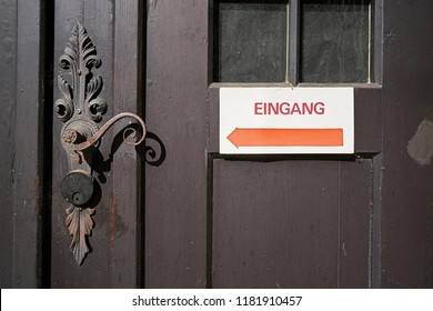 """Sign on a front door with the inscription """"Entrance"""" in the old town of Quedlinburg in Germany"""