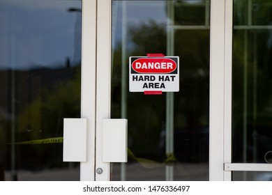 Sign on a glass door requiring hard hats for safety