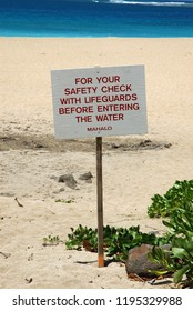 """A sign on a Hawaiian beach reads """"For your safety check with lifeguards before entering the water"""""""