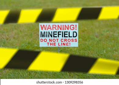 The sign on the lawn with the inscription WARNING! MINEFIELD DO NOT CROSS THI LINE closed prohibitory tapes