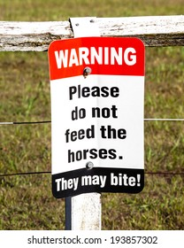 Sign on old peeling fence in front of grassy pasture stating WARNING Please do not feed the horses. They may bite!