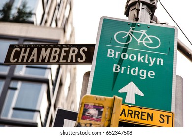 Sign on a post directing the way to the bicycle path of the Brooklyn Bridge.