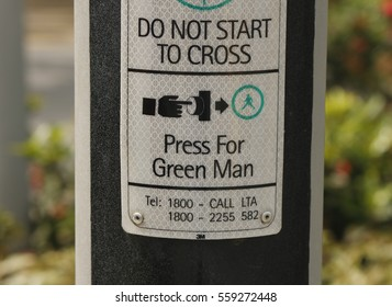 A sign on a post next to a pedestrian crossing showing how to press the button, in English, Singapore, November 2016