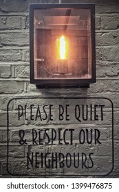 Sign on a pub wall reading 'Please be quiet and respect our neighbours'.