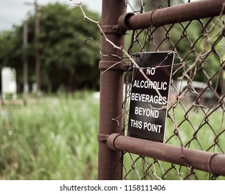 Sign on rusty fence - no alcoholic beverages beyond this point