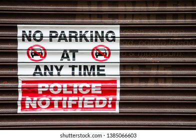 "Sign on a shop shutter ""No Parking at any time. Police Notified!"""