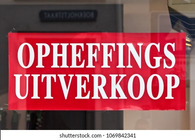 """Sign on a store window with the Dutch text """"liquidation sale"""""""