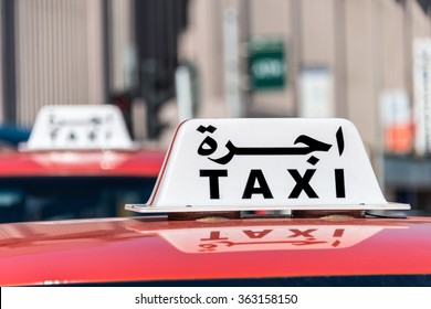 A sign on top of a red car says taxi in English and Arabic.