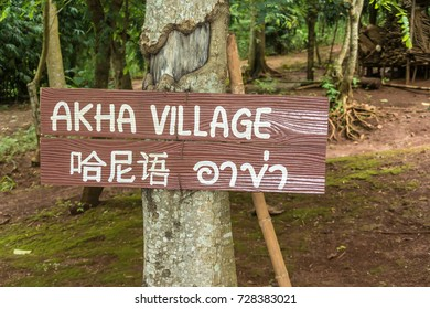 A sign on the tree indicating the direction to the village of Akha people in English, Akha language and another Asian language