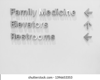 Sign on the wall at a Doctor's office pointing to different locations: Family Medicine, Elevators, Restrooms with arrows.