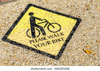 Sign Painted on a Sidewalk Telling Cyclists to walk their Bicycle.