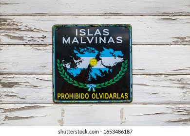 Sign plate with 'Islas Malvinas - forbidden to forget' words on old white wooden wall in Ushuaia port, Tierra del Fuego province, Argentina