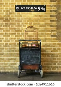 Sign with Platform 9 3/4 on it, above a trolley with suitcases and an empty bird cage against a brick wall