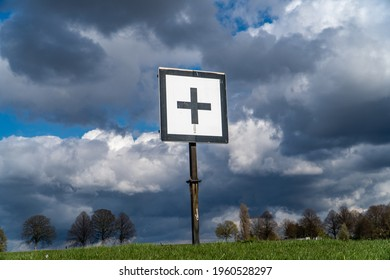 A sign with a plus sign on a stormy meadow
