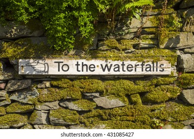 A sign pointing to the direction of Stock Ghyll Force waterfall in Ambleside, the Lake District.