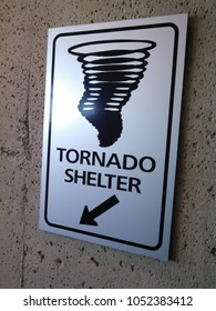 A sign points to a safe shelter in the event of a tornado or severe weather