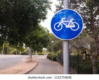 Sign post indicating the lane for bycicles with road and trees on background