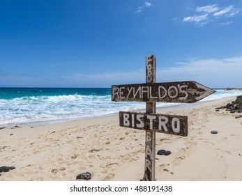 Sign post on a white sandy beach in front of a turquoise sea with deep blue skies and sun, leading to a restaurant, beach bar on Fuerteventura.