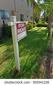 """A sign proclaiming """"FOR RENT"""" stands in front of an apartment building."""