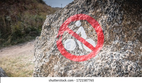 sign prohibiting cyclists painted on a rock by the sea