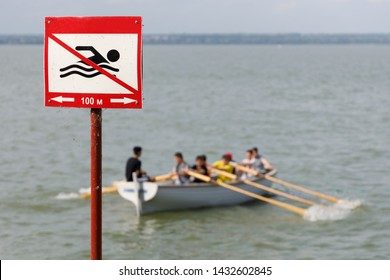 Sign prohibiting swimming in this place on the background of a wooden rowing boat with people