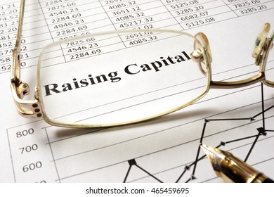 Sign raising capital on a paper and glasses.