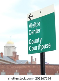 A  sign reading County Courthouse and Visitor Center with the courthouse in the background