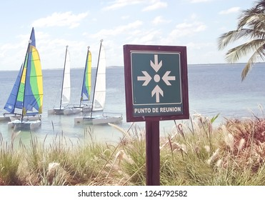 """Sign reading """"Meeting Point"""" in Spanish in tropical location with sailboats"""