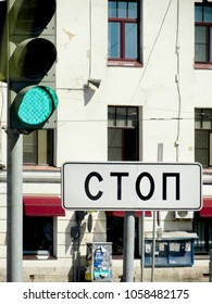 "Sign reading ""Stop"" in Russian with a Green Traffic Light"