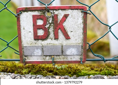 A sign with red letters BK. Letters B and K. The sign hangs crookedly relative to the horizon line. The sign associated with the electrification of housing in Norway.