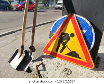 Sign of road works and two blades during repair of motorway