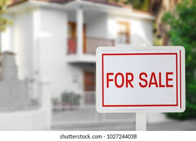 Sign FOR SALE in front of modern house outdoors. Real estate market