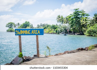 Sign for sea swimming area by Piula Cave Pool, Upolu Island, Western Samoa, South Pacific - lush tropical plants and foliage in background