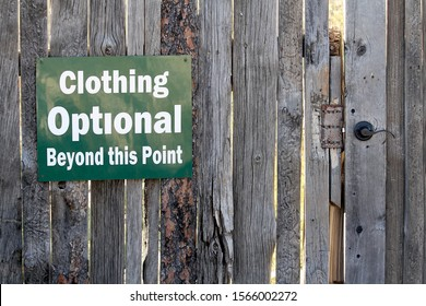 A sign showing Clothing Optional Beyond this Point.  This sign is posted on a rugged looking wood fence.  There is a door handle to the right of the sign,