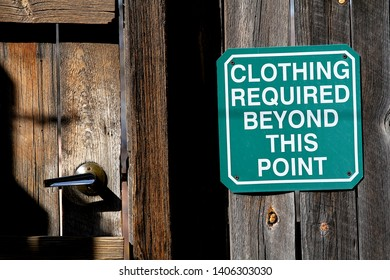 A sign showing clothing required beyond this point next to a wood door.