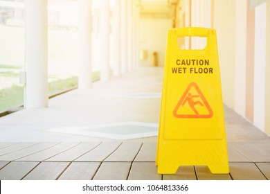 Sign showing warning of caution wet floor with walkway blur background and sunlight in summer time at high school or university. Selective focus and filtered process.