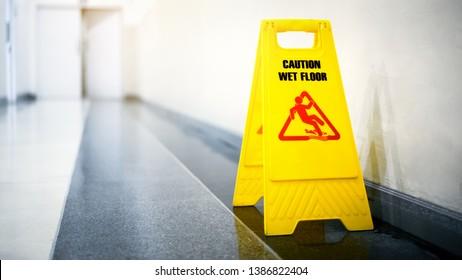 Sign showing warning of caution wet floor on wet tile floor