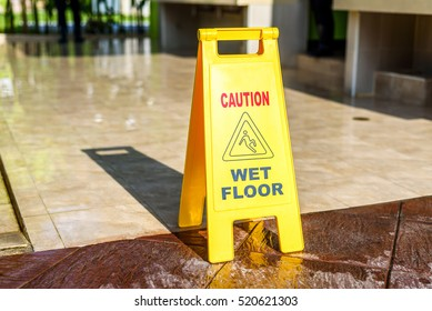Sign showing warning of caution wet floor on wet tile  floor in sunset