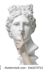 Sign of silence. Gypsum statue of Apollo's head with finger on lips. Eyes wide open. Statue. Silence. sssh. Verbosity. Quiet. Self-isolation. Coronavirus. Connection. Keep silence. The secret concept.