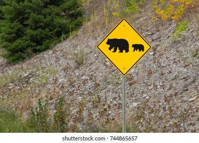 Sign, with silhouette of bear and young bear following, cautioning drivers on a Canadian highway of Bears crossing the road