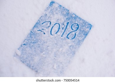 Sign in a snow- hand write 2018 on blue paper
