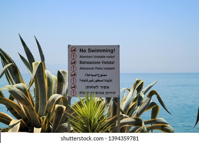 """Sign stating """"No Swimming!"""" in 8 languages is nestled amongst ornamental agave plants along the Sea of Galilee at Capernaum, Israel"""