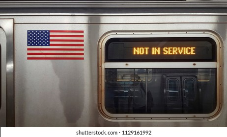 Sign stating not in service on NYC subway car with window and American flag