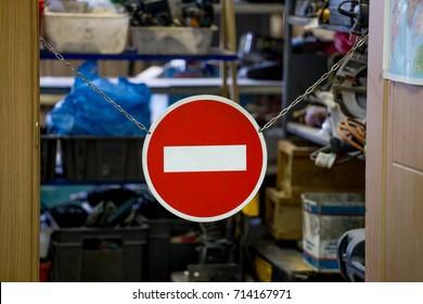 "The sign ""stop"" hangs in the doorway into workshop. Concept of restricted area."