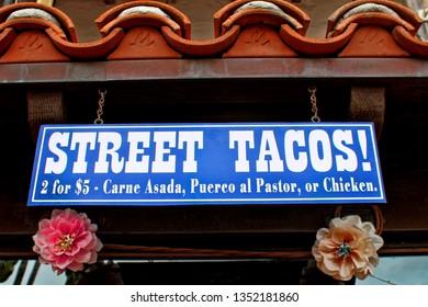 Sign for street tacos under a tile roof