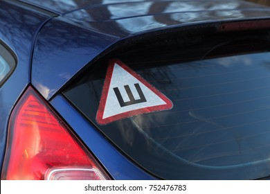 """Sign """"Studded tires"""" on the rear window of a car"""