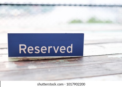 The sign 'Reserved' tag on the wooden table for the privilege private area for customer at the restaurant with blurred background with copy space