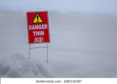 Sign talking about the dangers of thin ice near a frozen lake
