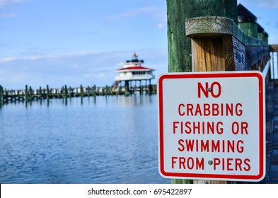 Sign telling visitors No Crabbing Fishing or Swimming from the Piers. Choptank River light house is intentionally blurred in the background.